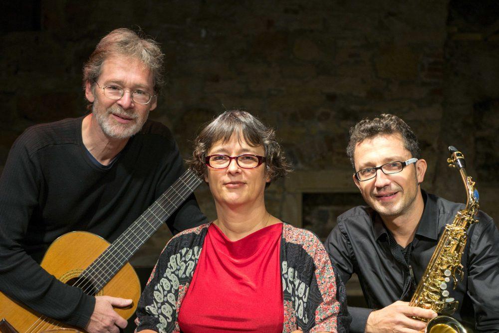 Ein Mann mit einer Gitarre, eine Frau und ein Mann mit Saxofon